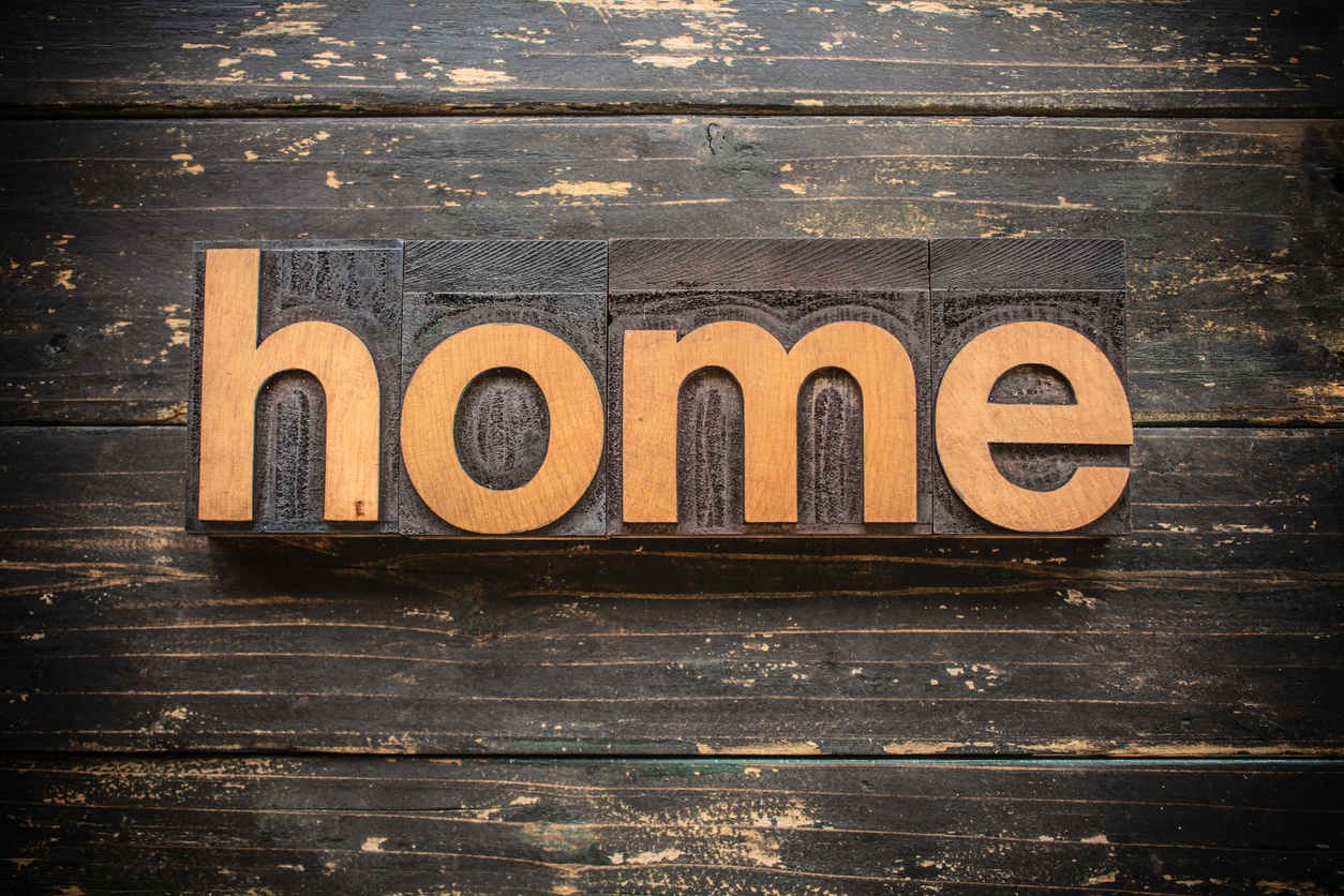 "The word ""HOME"" written in vintage wood letterpress type on a vintage rustic background."