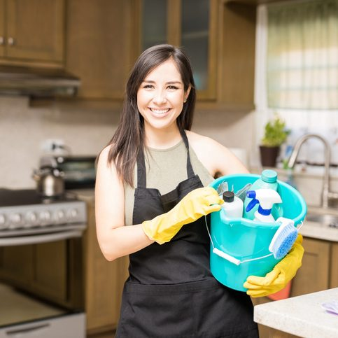 Happy house maid wearing black apron over casuals holding bucket filled with bottles of detergents, spray and disinfectant in kitchen
